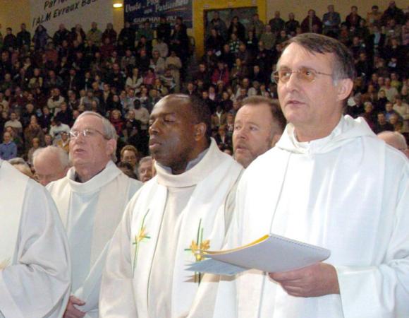 Le prêtre Wenceslas Munyeshyaka au milieu